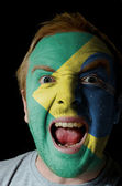 Face of crazy angry man painted in colors of Brazil flag — Stock Photo