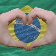 Heart and love gesture showed by hands over flag of Brazil backg — Stock Photo