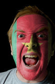 Face of crazy angry man painted in colors of Cameroon flag — Stock Photo