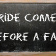 "Proverb ""Pride comes before a fall"" written on a blackboard — 图库照片"