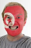 Faccia di pazzo uomo arrabbiato verniciato nei colori della bandiera della tunisia — Foto Stock