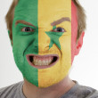 Face of crazy angry man painted in colors of senegal flag — Stock Photo