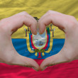 Stock Photo: Heart and love gesture showed by hands over flag of ecuador back