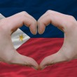 Heart and love gesture showed by hands over flag of phillipines — Stock Photo