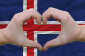 Heart and love gesture showed by hands over flag of iceland back — Stock Photo