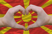 Heart and love gesture showed by hands over flag of macedonia ba — Stock Photo