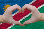 Heart and love gesture showed by hands over flag of namibia back — Stock Photo