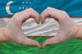 Geste de coeur et d'amour a montré par des mains sur le drapeau de l'ouzbékistan b — Photo