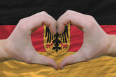 Heart and love gesture showed by hands over flag of germany back — ストック写真