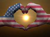 Heart and love gesture by hands colored in american flag during — Stock Photo