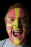 Face of crazy angry man painted in colors of macedonia flag — Stockfoto