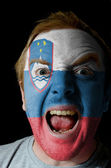 Face of crazy angry man painted in colors of slovenia flag — Stock Photo