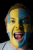 Face of crazy angry man painted in colors of sweden flag — Stock Photo