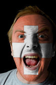 Face of crazy angry man painted in colors of swiss flag — Stockfoto