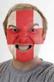 Face of crazy angry man painted in colors of england flag — Stock Photo