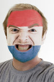 Face of crazy angry man painted in colors of holland flag — Stock Photo