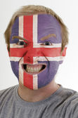 Face of crazy angry man painted in colors of iceland flag — Stock Photo
