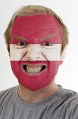 Ansikte av galet arg man målade i färgerna på lettlands flagga — Stockfoto