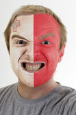 Face of crazy angry man painted in colors of malta flag — Stock Photo