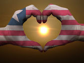 Heart and love gesture by hands colored in liberia flag during b — Stock Photo