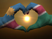 Heart and love gesture by hands colored in namibia flag during b — Stock Photo