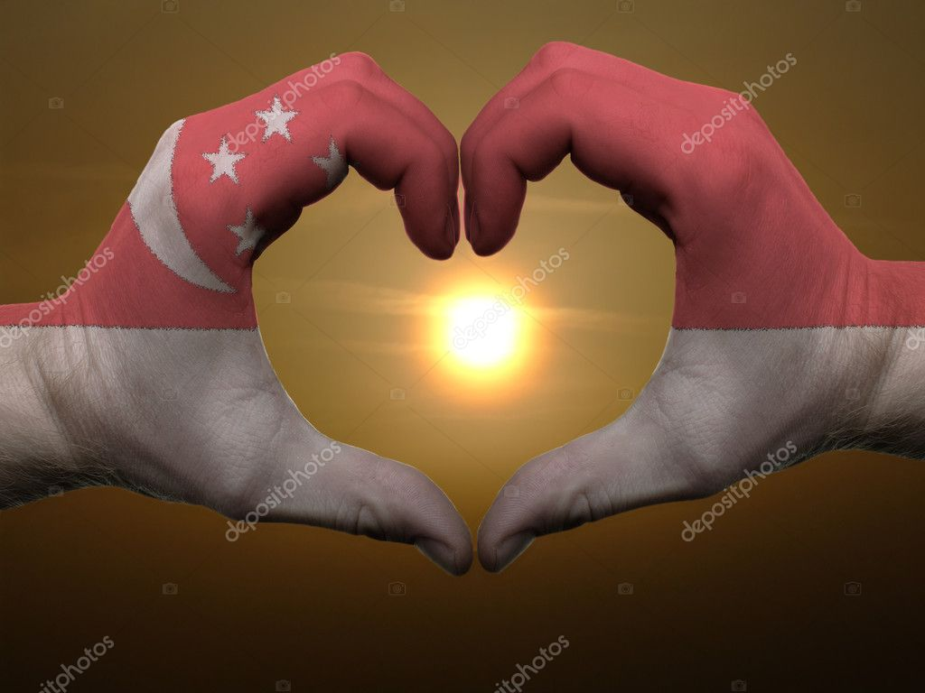 Gesture made by singapore flag colored hands showing symbol of heart and love during sunrise  Stock Photo #7559801