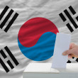 Man voting on elections in south korea in front of flag — Stock Photo