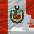 Stock Photo: Mvoting on elections in peru in front of flag