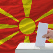 Stock Photo: Mvoting on elections in macedoniin front of flag