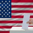 Stock Photo: Mvoting on elections in americin front of flag