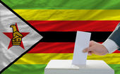 Man voting on elections in zimbabwe in front of flag — Stock Photo