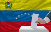 Man voting on elections in venezuela in front of flag — Foto Stock