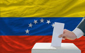 Man voting on elections in venezuela in front of flag — Foto de Stock