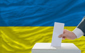 Man voting on elections in ukraine in front of flag — Stock Photo