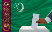 Man voting on elections in turkmenistan in front of flag — Stock Photo