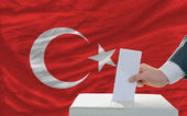 Man voting on elections in turkey in front of flag — Stock Photo