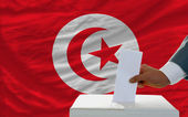 Man voting on elections in tunisia in front of flag — Stockfoto