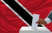 Man voting on elections in trinidad tobago in front of flag — Stock Photo