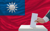 Man voting on elections in taiwan in front of flag — Stockfoto