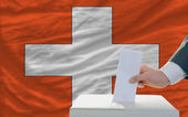 Man voting on elections in swiss in front of flag — Stock Photo