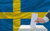 Man voting on elections in sweden in front of flag — Foto de Stock