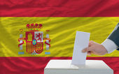 Man voting on elections in spain in front of flag — Stockfoto