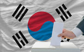 Man voting on elections in south korea in front of flag — Foto de Stock