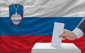 Man voting on elections in slovenia in front of flag — Stock Photo