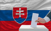 Man voting on elections in slovakia in front of flag — Stock Photo
