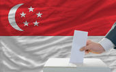 Man voting on elections in singaporel in front of flag — Stock Photo