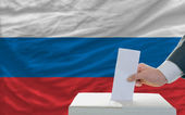 Man voting on elections in russia in front of flag — Stok fotoğraf