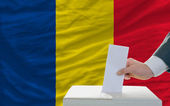 Man voting on elections in romania in front of flag — Foto de Stock