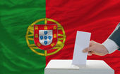 Man voting on elections in portugal in front of flag — Stok fotoğraf