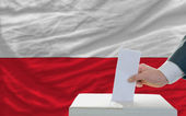 Man voting on elections in poland in front of flag — Stock Photo